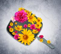 Frying pan with flowers - stock photo