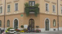 Lady walking in front of a flowershop in Ljubljana Stock Footage