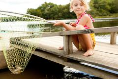 Girl on jetty with frog in fishing net Stock Photos