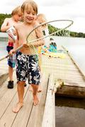 Boy with frog in a fishing net Stock Photos