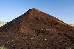 Mound of topsoil in commercial sandpit - stock photo
