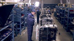 Stock Video Footage of Moving Conveyer with engines. Worker making truck engines