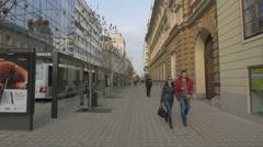People walking on the sidewalk by the bus stop in Ljubljana Stock Footage