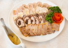 Assortment of sliced meat, chicken and pork rolls. Saucepan with sauce. Stock Photos