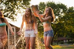Girl pouring bucket of water over friend's head Stock Photos