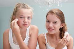 Teenage girls cleansing their faces Stock Photos