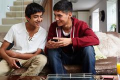 Teenage boys looking at cellphone Stock Photos