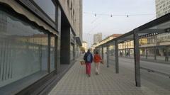 Man and woman with baskets walking on Slovenska street in Ljubljana Stock Footage