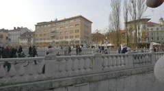 Tourists and locals walking on Triple Bridge in Ljubljana Stock Footage