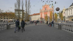 Family with baby in the stroller crossing the Triple Bridge in Ljubljana - stock footage