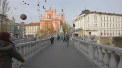 Old lady with a cane crossing the Triple Bridge in Ljubljana Stock Footage