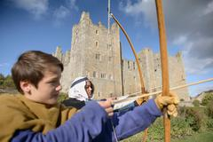 History students in period dress practising archery outside Bolton Castle, a - stock photo