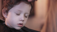 Hairdresser cutting hair of child in Barbershop Stock Footage