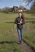 Young parish priest walking in her countryside parish - stock photo