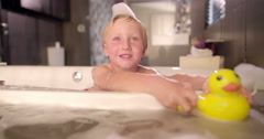 Little Boy Playing with Rubber Duckies in Bubble Bath Stock Footage