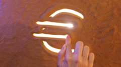Hand drawing Euro symbol in the sand. Beach background. Top view Stock Footage