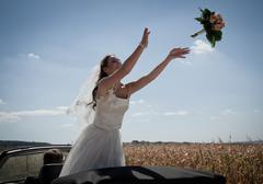 Newlywed bride tossing bouquet from car Stock Photos