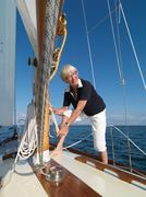 Woman adjusting rigging on sailboat Stock Photos