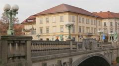 A few people walking on the Dragon Bridge in Ljubljana Stock Footage