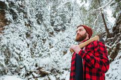 Handsome bearded young man with axe in winter forest Stock Photos