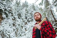 Serious man holding axe and walking in winter forest - stock photo