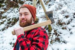 Smiling attractive bearded man with axe in winter forest Stock Photos