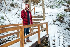 Bearded man with axe standing on wooden bridge in winter Stock Photos
