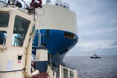 Tugs and ship at sea - stock photo