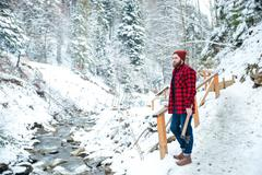 Man standing near mountain river and holding axe in winter - stock photo