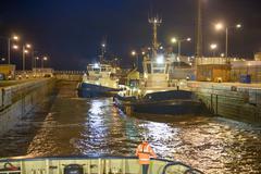 Tugs in lock at night, high angle - stock photo