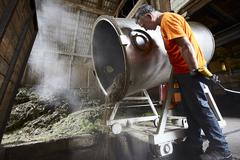 Stock Photo of Worker pouring mixture from vat in shop
