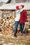 Happy woman hugging handsome man with axe in village - stock photo