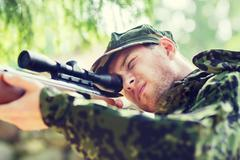 young soldier or hunter with gun in forest - stock photo