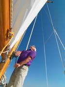 Man adjusting rigging on sailboat Stock Photos