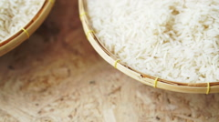 Rice in a rattan bowl on light plywood table. Organic agricultural concept Stock Footage