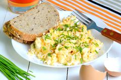 Scrambled eggs with wholemeal bread and fresh chives - stock photo