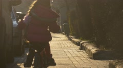 Little Girl is Riding the Bike Away Along Street in Opole Poland  Stock Footage