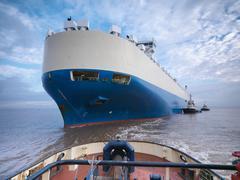 Tugs pushing large ship out at sea - stock photo