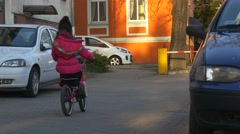 Little Girl is Riding a Bike by Courtyard Cars Are Parked Residental House in Stock Footage