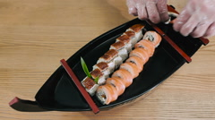 Sushi master puts sushi and wasabi on a plate - stock footage