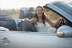 Newlywed bride sitting in convertible Stock Photos