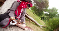 Boy dressing up as pirate sitting on log reading map - stock footage