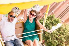 Couple riding amusement park ride Kuvituskuvat