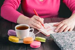 Woman write letter i love you while drinking coffee Stock Photos