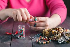 Relax hobby. Female make craft beads - stock photo
