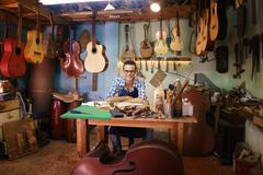 Portrait Of Happy Artisan Lute Maker In Guitar Shop Smiling At Camera - stock photo