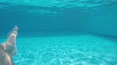 A guy is swimming at swimmingpool / under water and just see legs Stock Footage
