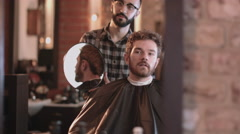 Barber in hairdresser showing client hair cut Stock Footage