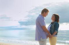 Couple holding hands on beach Stock Photos