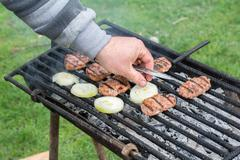 Outdoor barbecue. Men's hand baked meatballs on the grill. Stock Photos